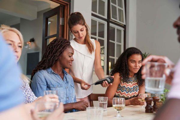 Female customer in restaurant paying bill using chip pin machine