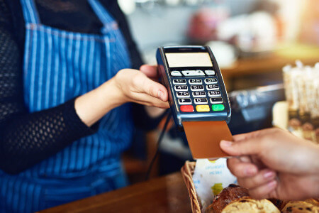 retail customer paying at till with card machine